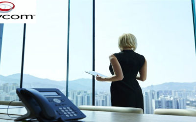 Polycom phone on desk with woman looking at skyline through office window